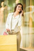 picture of shopping center  - Beauty woman with shopping bags in shopping mall is talking by phone - JPG