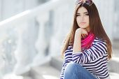 foto of straight jacket  - Beautiful young girl, Caucasian appearance, with dark, long, straight hair, brown eyes and beautiful dark eyebrows, wearing a striped shirt, blue jeans, wearing pink neck scarf, sitting outdoors on stairs in the city.
