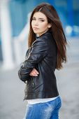 stock photo of straight jacket  - Beautiful young girl, Caucasian appearance, with dark, long, straight hair, brown eyes and beautiful dark eyebrows, wearing a striped shirt, blue jeans and black leather jacket, standing in the street, near the blue building with white railings