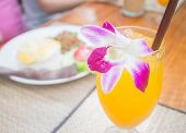 Glass Of Iced Orange Juice decorated with orchid