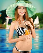 Young woman in swimsuit with cocktail on swimming pool background