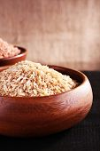 Grains of rice in bowls on table on sackcloth background