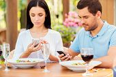 stock photo of envy  - Young couple typing something on their smart phones while relaxing in outdoors restaurant together - JPG