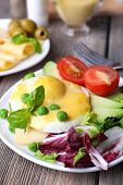 foto of benediction  - Toast with egg Benedict and avocado on plate on wooden table - JPG