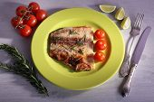 Dish of Pangasius fillet with rosemary and cherry tomatoes in plate on color wooden table background