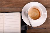 Cup of coffee on saucer with diary and spoon on wooden table background