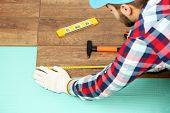 picture of laminate  - Carpenter worker installing laminate flooring in the room - JPG