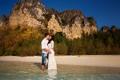 image of barefoot  - bride and groom barefoot at edge of transparent water against cliffs and tropical trees - JPG