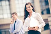 pic of business-partner  - Young business partners standing in front of the building. Business woman carrying laptop while her partner use a mobile phone for business conversation. ** Note: Visible grain at 100%, best at smaller sizes - JPG