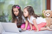 stock photo of three sisters  - Cute little sisters using laptop on bed at home - JPG