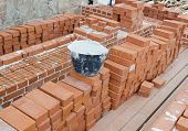picture of brick block  - Mason bricklaying background with bucket of cement and clay brick blocks - JPG