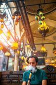 image of shisha  - Man smoking turkish hookah in the cafe with coloful lamps on background in Istanbul - JPG
