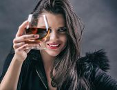 pic of forlorn  - Young beautiful woman in depression drinking alcohol on dark background - JPG