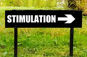 stock photo of stimulation  - STIMULATION written on directional black metal sign with arrow pointing to the right against natural green  background - JPG