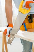 image of sawing  - Midsection of man sawing wood in new house - JPG