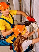 picture of millwright  - Happy group builder in uniform drilled wall - JPG