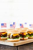 picture of beef-burger  - Mini beef burgers with American flag on wooden boardselective focus and blank space - JPG