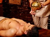 picture of panchakarma  - Young  handome man having Ayurveda spa treatment with pouring oil on head - JPG