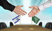 stock photo of saudi arabia  - Two diplomats from Israel and Saudi Arabia extending their hands for a handshake on an agreement between the countries - JPG