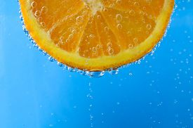 picture of suspenders  - Close up of a fresh orange slice at top of image and facing forwards suspended in sparkling bright blue water - JPG