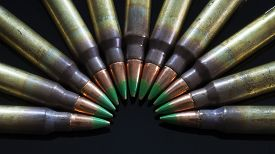 stock photo of semi-circle  - Rifle ammunition that has green tipped bullets in a semi circle on black - JPG