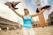 foto of beautiful young woman  - Beautiful young woman feeding pigeons - JPG