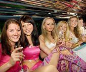 Grupo de mujeres hermosas tintineo de copas con champán dentro de una limusina