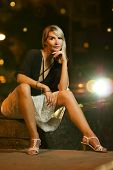 Beautiful young woman sitting on a street. Car lights behind her