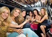 Group of beautiful women clinking glasses with champagne inside a limousine