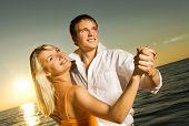 Постер, плакат: Молодая пара танцы на берегу океана на закате