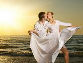 picture of kissing couple  - Young couple in love on a beach at sunset - JPG