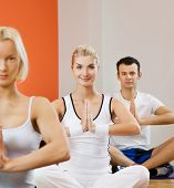 Group of people doing yoga exercise (focus on a woman in the middle)