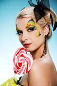 Young beauty with butterfly face-art heart shaped lollipop