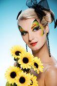 Joven belleza con cara de mariposa-arte y ramo de girasoles
