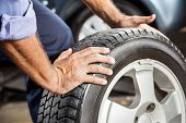 Mechanic Holding Car Tire At Garage poster