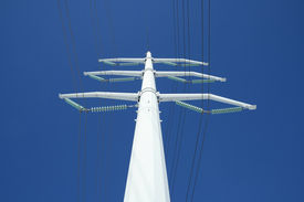 pic of electricity pylon  - white high voltage electricity pylon against the deep blue sky from below - JPG