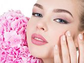 Young woman touches cheek by fingers. Young beautiful woman with flowers near face. Beauty treatment poster