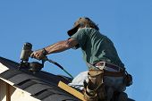 picture of shingles  - a roofer on a roof putting down shingles - JPG
