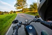 POV of motorbiker holding steering bar, riding in beautiful sunset light. Travel and freedom, outdoo poster