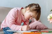 Child With Down Syndrome Enthusiastically Drawing With Colorful Pencils poster