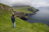 Photographer taking pictures on Mykines, Faroe Islands