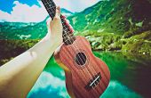 Romantic View Of The Ukulele Guitar Hold In A Hand, Mountains On Background . Photo Depicts Musical poster