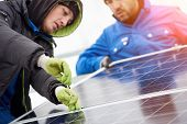 Technicians In Blue Suits Mounting Photovoltaic Solar Panels On Roof Of Modern Houses. Solar Modules poster