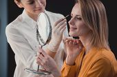 Smiling Visagiste Painting Brows Of Glad Young Woman. She Watching At Reflection. Glad Professional  poster