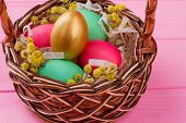 Easter Eggs And Pussy-willow In Woven Basket. Gold Egg And Colorful Eggs Decorated With Pussy-willow poster