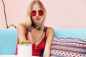 Blonde Female With Serious Look Wears Red Sunglasses, Tank Top, And Bandana On Neck, Poses In Cozy R poster