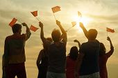 Happy Turkish Family With Flags. Patriotic People Raising Flags To The Evening Sky, Back View. poster