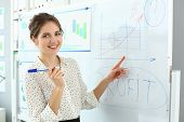 Portrait Of Smart Lady Pointing At Important Business Charts And Graphs On High-tech Glass Board. At poster