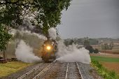 Steam Freight Train Blowing Black Smoke And White Steam While Traveling Through The Countryside poster