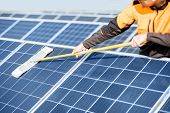 Professional Cleaner In Protective Workwear Cleaning Solar Panels With A Mob. Concept Of Solar Power poster